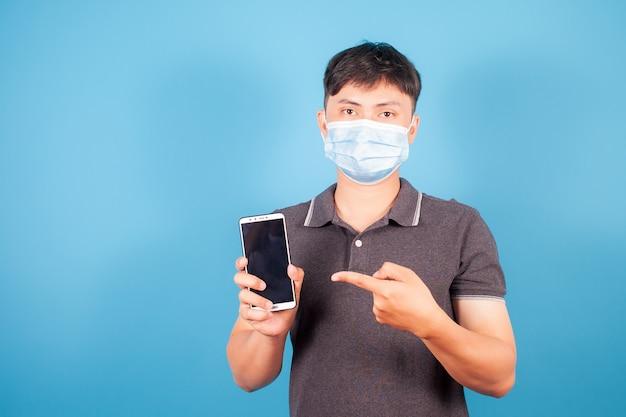 Azjatycki portret młody biały człowiek nosić maskę stojącą nosić koszulę, co palcem wskazującym na inteligentny cyfrowy telefon komórkowy pusty ekran na niebieskim tle
