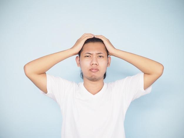 Azjatycki poważny młody człowiek martwi się i dostaje ból głowy.