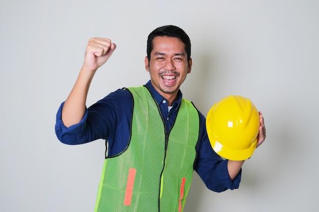 Azjatycki pracownik budowlany dopingujący, trzymając żółty kask ochronny
