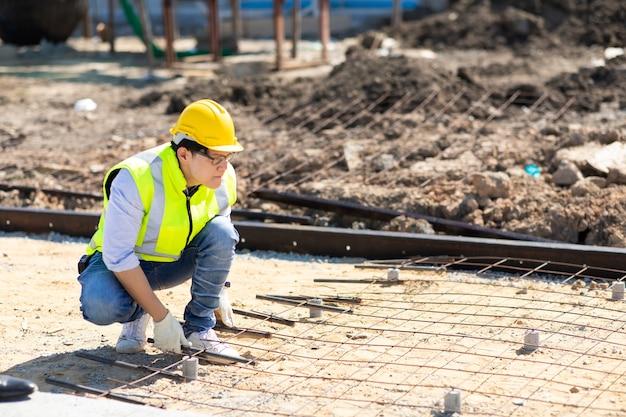 Azjatycki pracownik budowlany na budowie. wytwarzanie prętów zbrojeniowych ze stali