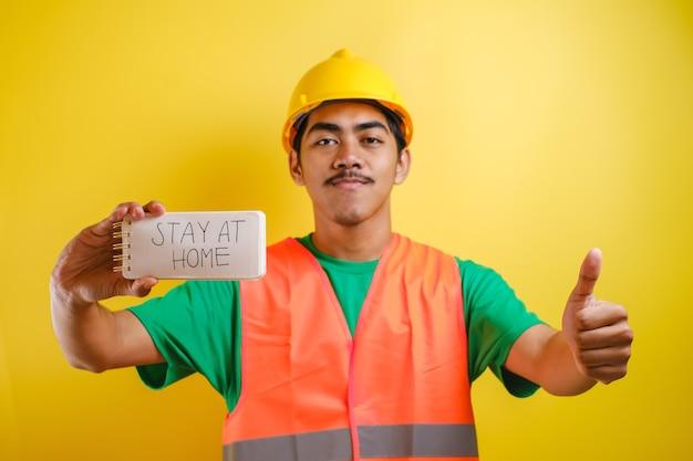 """Azjatycki pracownik budowlany trzyma notatki z napisem """"zostań w domu"""", podczas gdy kciuk w lewą rękę, uśmiechy patrzył na aparat na żółtym tle"""