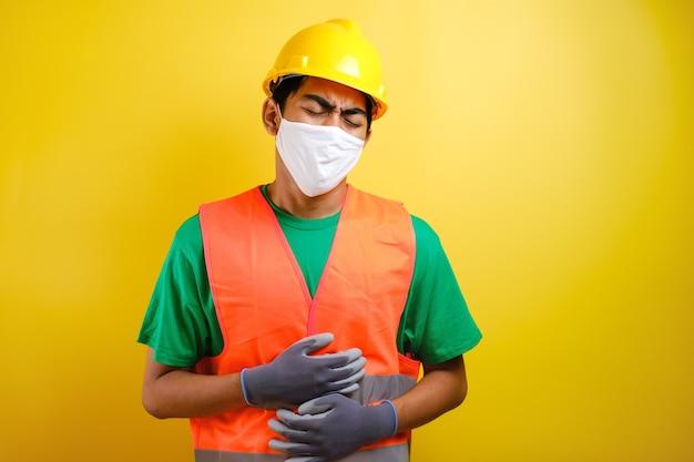 Azjatycki pracownik budowlany ubrany w kask ochronny i maskę ochronną na żółtym tle z ręką na brzuchu, ponieważ niestrawność, bolesna choroba źle się czuje. koncepcja bólu.