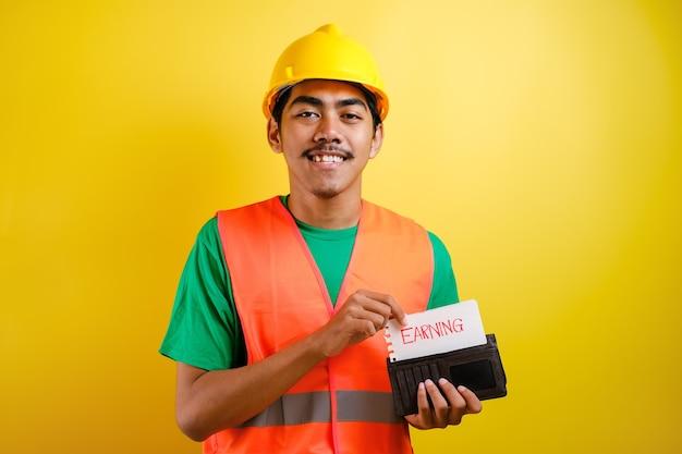"""Azjatycki pracownik budowlany uśmiecha się do kamery, wkładając do portfela coś z napisem """"zarabianie"""". mężczyzna pokazał gest odłożenia części pensji na ratunek"""
