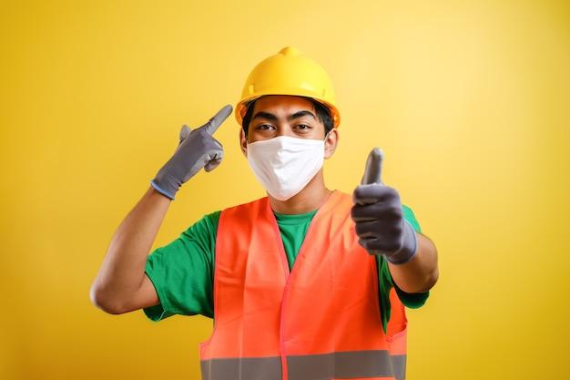 Azjatycki pracownik budowlany wskazujący na swoją maskę ochronną i hełm ochronny zachęca do priorytetowego traktowania zdrowia i bezpieczeństwa na żółtym tle