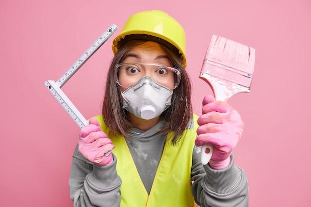 Azjatycki pracownik kobieta z pędzlem i mundurem. pracownik budownictwa przemysłowego lub remontu domu