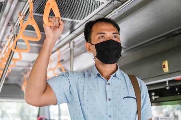 Azjatycki pracownik noszący maskę do ochrony pasażerów komunikacji miejskiej w tramwaju