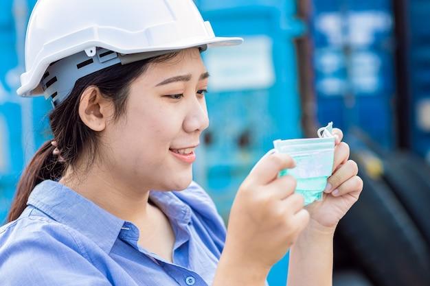 Azjatycki pracownik noszący maskę na twarz do ochrony przed pyłem i wirusem koronowym podczas pracy w miejscu pracy.