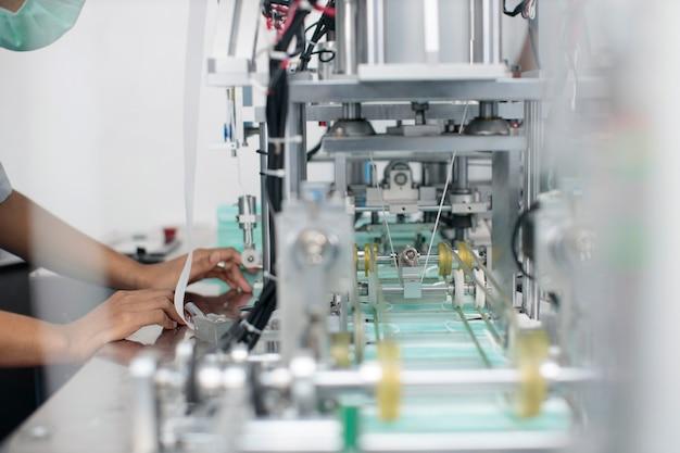 Azjatycki pracownik ręce kontroli jakości linii produkcyjnej masek i masek medycznych, koncepcji przemysłu i fabryki.
