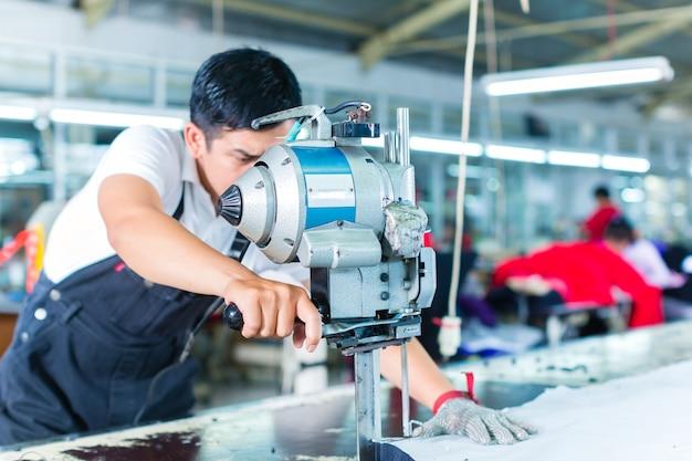 Azjatycki pracownik używa maszynę w fabryce
