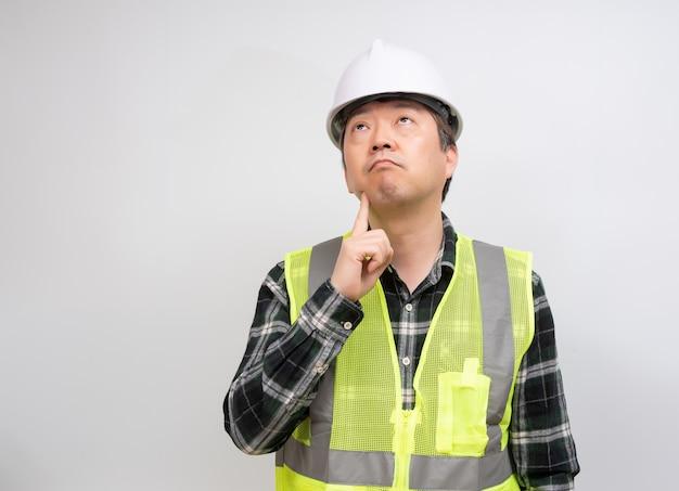 Azjatycki pracownik w średnim wieku, który dokładnie się nad czymś zastanawia.