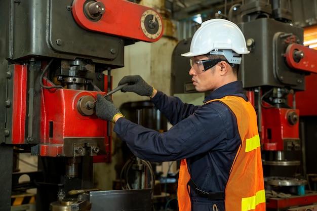 Azjatycki pracownik w zbawczym kapeluszu w maszyneria pokoju pracuje z maszyną na fabryce.