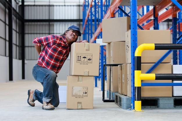 Azjatycki pracownika mężczyzna krzywdził jego tylnego podnośnika ciężkiego pudełko w fabryce