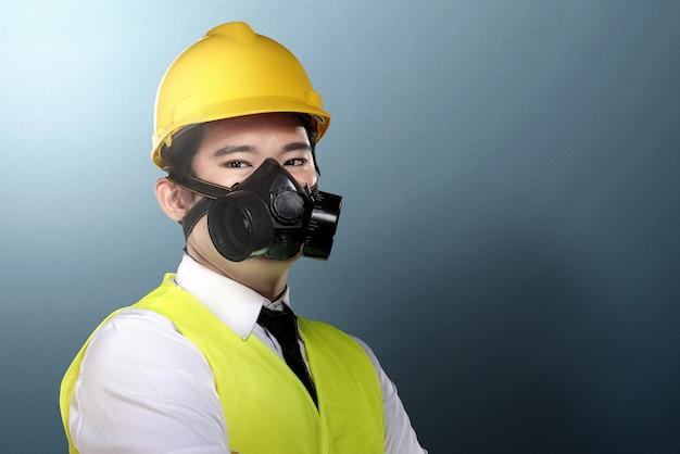 Azjatycki pracownika mężczyzna z maską ochronną i żółtą hełm pozycją