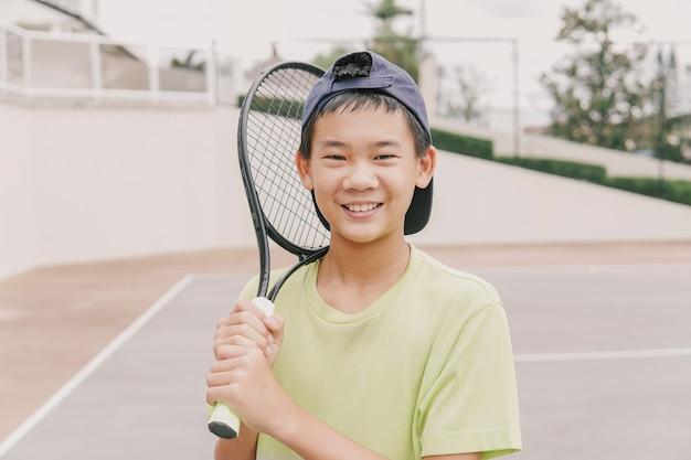 Azjatycki preteen chłopiec gra w tenisa, trening zdrowych młodych sportowców, koncepcja aktywnego dobrego samopoczucia
