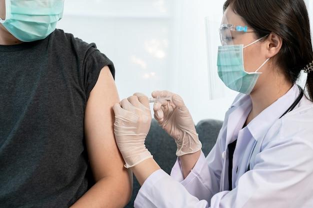Azjatycki profesjonalny lekarz wstrzykujący szczepionkę przeciwko koronawirusowi 2019-ncov lub covid-19 w ramię pacjenta płci męskiej z bliska, covid19 szczepiący się w celu ochrony i budowy przeciwciała - odporności przeciwko koronawirusowi.