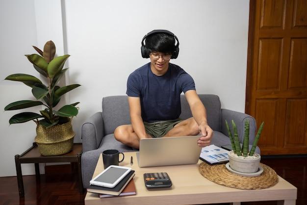 Azjatycki przedsiębiorca pracuje w domu nad jakimś projektem ze swoim laptopem w domu