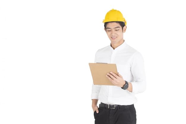 Azjatycki przystojny biznesmen jest ubranym żółtego zbawczego hełm patrzeje dokument na schowku w jego ręki zakończeniu i czyta up, odizolowywający na białym białym copyspace.