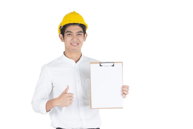 Azjatycki przystojny biznesmen jest ubranym żółtego zbawczego hełm trzyma kciuk w górę schowka w jego ręki zakończeniu i pokazuje up, odizolowywający na białym białym copyspace.
