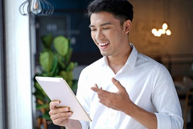 Azjatycki przystojny biznesmen lub młody student za pomocą komputera typu tablet