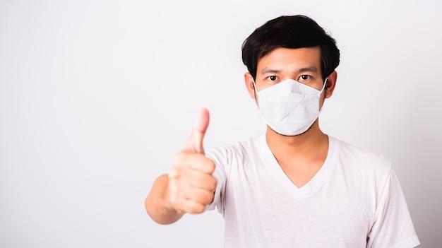 Azjatycki przystojny mężczyzna jest ubranym ochronną sukienną twarz maskę przeciw koronawirusowi pokazuje palcowego kciuk dla dobrego znaka