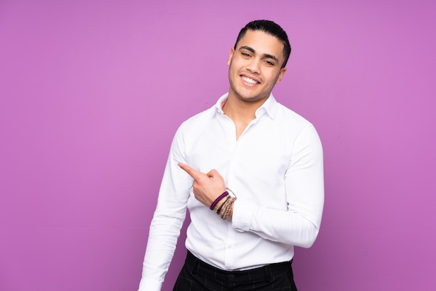 Azjatycki przystojny mężczyzna na białym tle na niebieskiej ścianie, wskazując w bok, aby przedstawić produkt