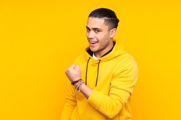 Azjatycki przystojny mężczyzna na białym tle na żółtej ścianie śmiejąc się w pozycji bocznej