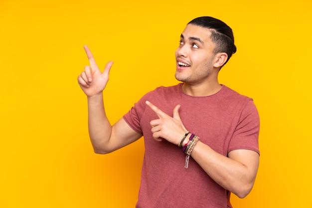 Azjatycki przystojny mężczyzna na białym tle na żółtej ścianie, wskazując na bok i robi gest ciszy