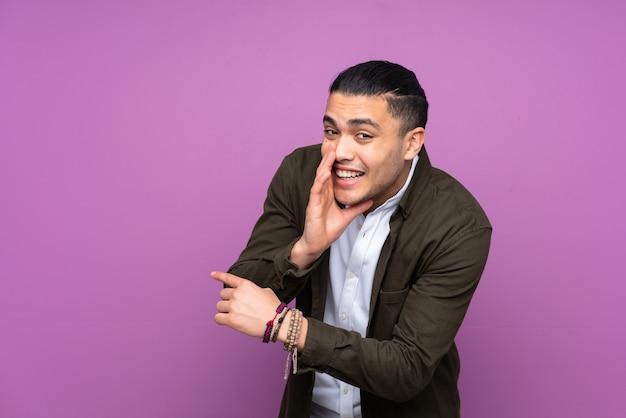 Azjatycki przystojny mężczyzna na niebieskiej ścianie, wskazując w bok, aby przedstawić produkt i coś szeptać