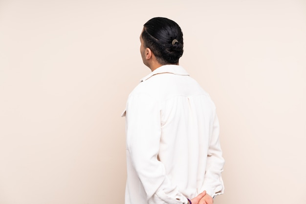 Azjatycki przystojny mężczyzna nad ścianą w tylnej pozycji i patrząc wstecz