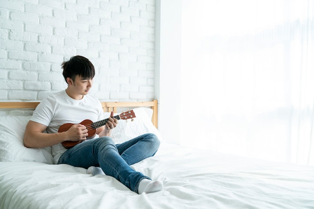 Azjatycki przystojny mężczyzna siedzi na łóżku i gra na gitarze ukulele w relaksujący dzień w domu