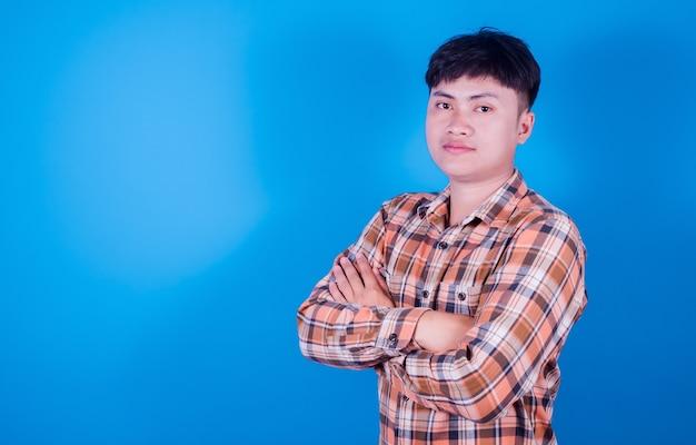 Azjatycki przystojny młody mężczyzna stojący nosi pasiastą koszulę z założonymi rękoma, patrząc na kamerę na niebieskim tle