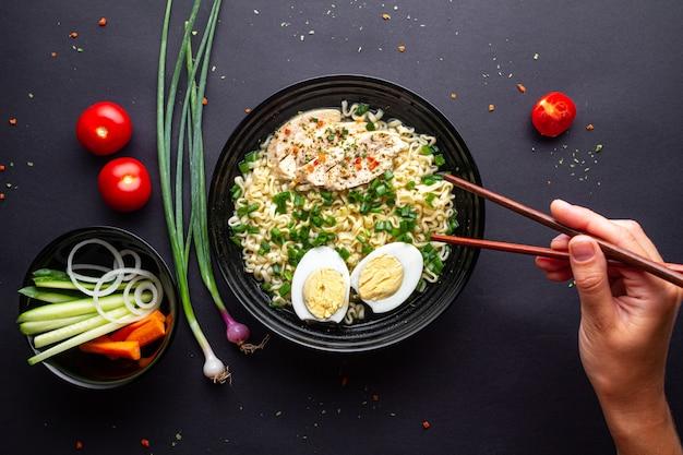 Azjatycki ramen zupny puchar na czarnym tle. makaron z kurczakiem, warzywami i jajkiem w czarnej misce. widok z góry.