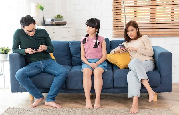 Azjatycki rodzic korzystający z tabletów i telefonów komórkowych w domu uzależniony od urządzeń