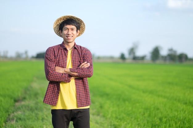 Azjatycki rolnik mężczyzna stojący ze skrzyżowanymi ramionami na farmie zielonego ryżu