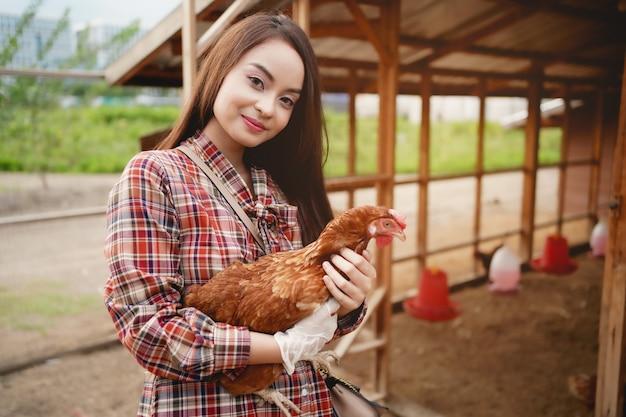 Azjatycki rolnik trzyma kurczaka w gospodarstwie kurczaków