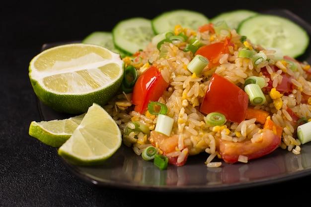 Azjatycki ryż khao pad kung smażony z warzywami, mięsem, jajkiem, świeżymi ogórkami i pomidorami