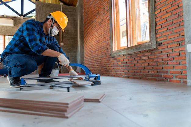 Azjatycki rzemieślnik glazurnik na placu budowy, pracownik tnie dużą płytę płytek podczas budowy domu, sprzęt do cięcia płytek podłogowych