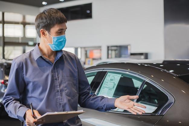 Azjatycki saleman nosi maskę chirurgiczną pracującą w inspektorze sprawdzającym pisanie w schowku w garażu dealerskim