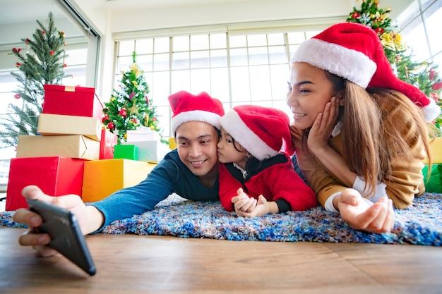Azjatycki selfie trzymając smartfon robienie zdjęć. szczęśliwa młoda rodzina z dzieciakami zabawy z okazji bożego narodzenia. czas świąt. mój tata, mama i córka w mikołajowych czapkach kłamią z przodu pudełko prezentowe w domu.