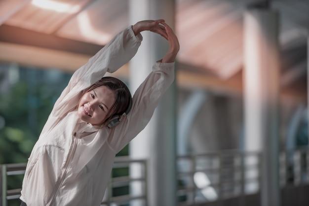 Azjatycki sport kobiety rozciąganie wręcza plenerowego.