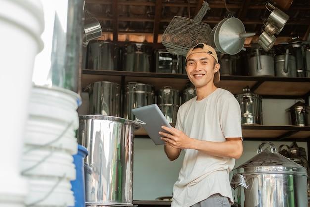 Azjatycki sprzedawca stoi w pobliżu dużej patelni podczas korzystania z tabletu i patrzy na aparat w sklepie agd