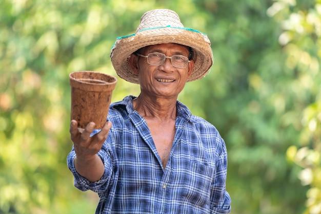 Azjatycki średniorolny rolnictwa mienia garnek.