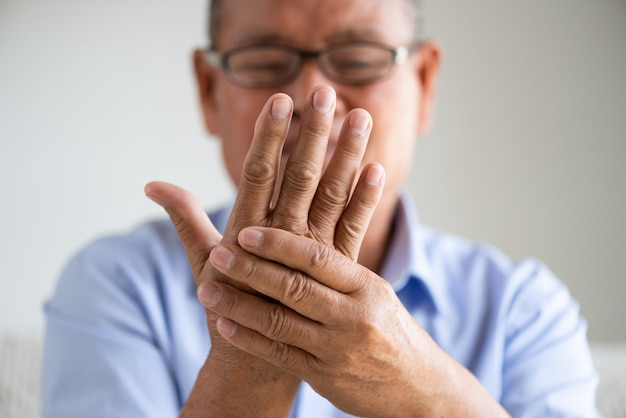 Azjatycki starego człowieka obsiadanie na kanapie i mieć ręka ból