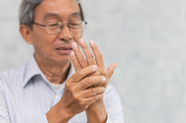 Azjatycki starszy cierpi na ból mięśni ścięgna dłoni.
