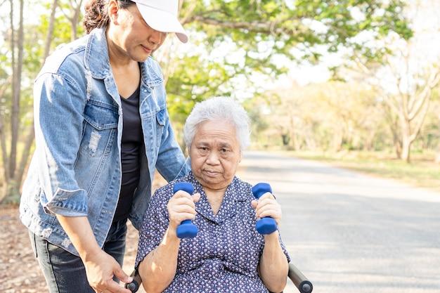 Azjatycki starszy kobieta ćwiczenia pacjenta z hantlami na wózku inwalidzkim.