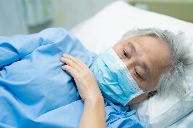 Azjatycki starszy kobieta pacjent jest ubranym maskę w szpitalu dla gacenia od coronavirus