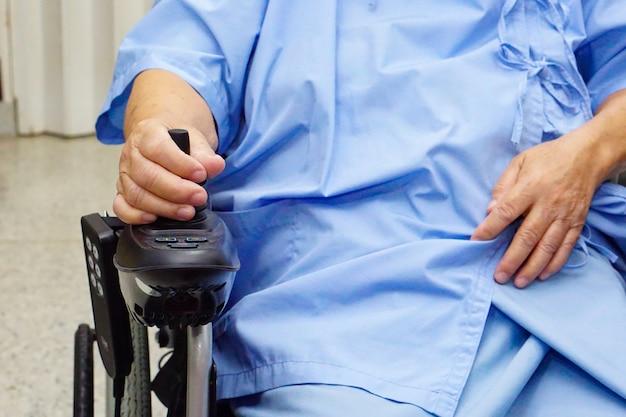 Azjatycki starszy kobieta pacjent na elektrycznym wózku inwalidzkim z pilot do tv przy szpitalem.