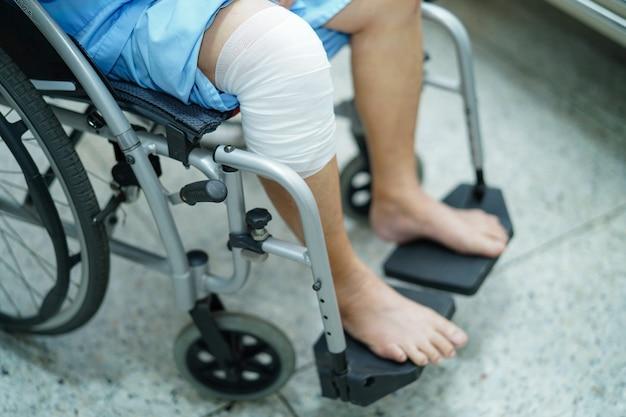 Azjatycki starszy kobieta pacjent na wózku inwalidzkim przy szpitalem.