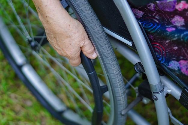 Azjatycki starszy kobieta pacjent na wózku inwalidzkim w parku.
