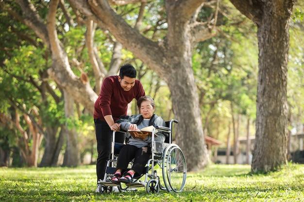 Azjatycki starszy kobiety obsiadanie na wózku inwalidzkim z jej syna uśmiechu szczęśliwą twarzą na zielonym parku